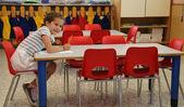 Uśmiechnięte dziewczyny pisze na biurku szkoły — Zdjęcie stockowe
