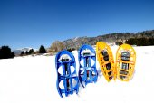 Four blue and orange snowshoes in mountains — Stock Photo