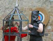 Medieval EXECUTIONER with black cap on head and girl in cage — Stock Photo
