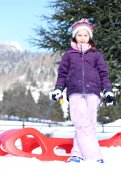 Pretty girl plays with red sled in the mountains in the snow — Stock Photo