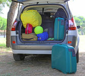 Car and plenty of luggage and suitcases when leaving for family summer holidays — Stock Photo