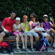 Happy family of five people eat sandwiches on a bench — Stock Photo #78706686