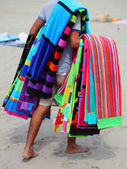 African peddler of towels and beach towels on the beach in summe — Stock Photo