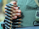 Soldier in uniform with bullets in his hand ready to open fire — Stock Photo