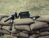 Great machine gun with bullets over the sandbags — Stock Photo