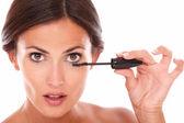 Afraid woman with brown eyes applying mascara — Foto de Stock