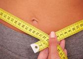 Sporty young girl getting waist measurement — Stok fotoğraf