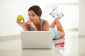 Sporty young woman browsing web and laying — Stock Photo