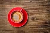 View of coffee in red cup on wooden vintage table — Stock Photo