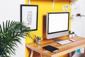 Modern creative workspace on yellow wall.  — Stock Photo