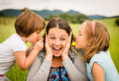 Children blowing whistle to mothers ears — Stock Photo