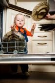 Baby helping unload dishwasher — Stock Photo
