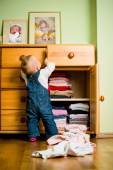 Domestic chores - baby throws out clothes — Stock Photo