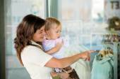 Mother with baby at shop window — Stock Photo