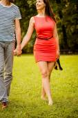 Young couple walking on grass — Fotografia Stock