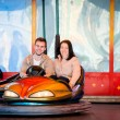 Young couple riding car in amusement park — Stock Photo #69698815