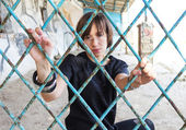 A girl behind the iron bars — Stock Photo