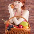 Redhead girl with a basket of fruits — Stock Photo #56131069