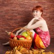 Redhead girl with a basket of fruits — Stock Photo #56131061
