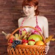 Redhead girl with a basket of fruits — Stock Photo #56131065