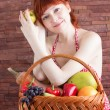 Redhead girl with a basket of fruits — Stock Photo #56131077