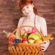 Redhead girl with a basket of fruits — Stock Photo #56131397