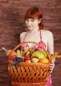 Redhead girl with a basket of fruits — ストック写真