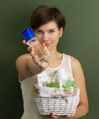 Woman with a basket full of skin care products — Stock Photo