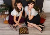 Two beautiful girl friends playing chess by the fireplace — Stock Photo