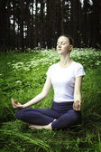Young girl practicing yoga in a forest — Stock Photo