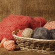 Multicolored yarn balls in a straw basket on the sacking — Stock Photo #52168827
