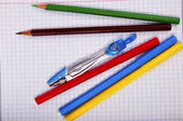 Pencils, pen, compass on exercise book page — Stock Photo
