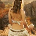 Постер, плакат: Primitive woman sitting on a rock at the sunset Amazon woman