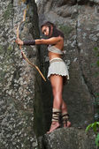 Primitive woman standing on a rock and holding a bow. Amazon woman — Stock Photo
