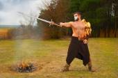 Portrait of a muscular ancient warrior with a sword — Stock Photo