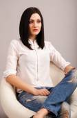 Woman in jeans sitting on chair — Stock Photo