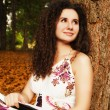 Brunette beautiful woman reading book in the forest — Stock Photo #74282563