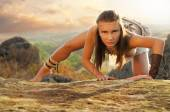 Primitive woman on a rock at the sunset. Amazon woman — Stock Photo