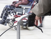 Man with walking frame and wheelchair — Stock Photo