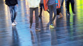 People walking on wet pavement — Stock Photo