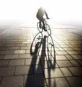 在夕光背点亮骑自行车的人 — 图库照片