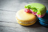 Eat of macaron closeup on wooden — Стоковое фото