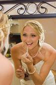 Bride add some lip gloss — Stock Photo