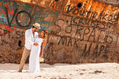 Young couple in a beach with shipwreck — Stockfoto