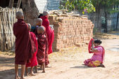 Woman gives alms to novice monks — Stock Photo