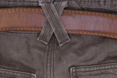 Brown jeans with a belt and binding. Close-up of men's clothing. — Stock Photo