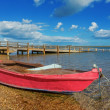 Red fishing boat on the shore. Near the bridge. — Stock Photo #57638543