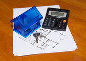 Toy house and calculator on table — Stock Photo