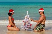 Sexy girl man Santa on a beach fir-tree — Stock Photo