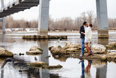 loving couple on the river bank embraces, kisses — Stockfoto